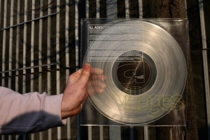 "Picture of a hand, holding the second press of the Villages ""ILL AGES"" LP in front of an iron gate"