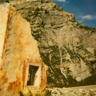 "Cover of the Little Gold ""On The Knife"" LP. It shows a part of a sandstone wall with a window (just containing an iron cross and no glass, like a jail window) and a mountain in the background."